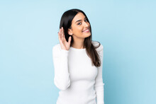 Young Caucasian Woman Isolated On Blue Background Listening To Something By Putting Hand On The Ear