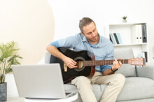 A Young Man Is Learning Playing Guitar Himself, Watching Webinar, Online Masterclass, Video Tutorial. A Guy Holds Acoustic Guitar And Repeat Exercises, Laptop In Front Of Him. E-learning Concept