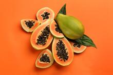Fresh Ripe Papaya Fruits With Green Leaves On Orange Background, Flat Lay