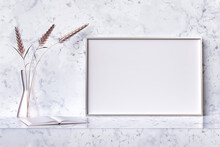Picture Frame Mockup On A White Marble Stand With An Opened Book And A Decorative Crystal Vase With Rose Golden Wheat Spikelets. Fine Art Style 3d Render Illustration.