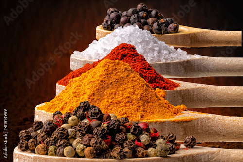 Fototapeta Colorful spices placed on kitchen wooden spoons in perspective. Still life suitable for a cookbook, cover, obraz