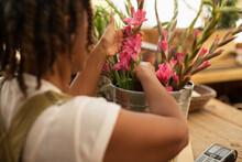 Female Florist Arranging Pink Flowers In Bucket In Shop