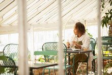 Female Garden Shop Owner Drinking Tea At Table In Greenhouse