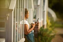 Female Plant Nursery Owner Taking Coffee Break At Sunny Greenhouse