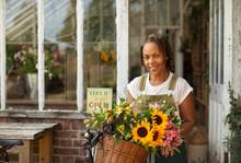Portrait Female Florist With Flowers In Bike Basket Outside Shop