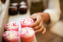 Close Up Hand Reaching For Pink Cupcake