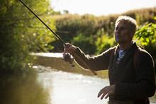 Man Casting Fly Fishing Pole At Sunny Idyllic River