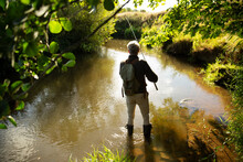 Man With Backpack Fly Fishing At Sunny River