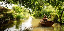 Man Fly Fishing From Boat On Tranquil Green River