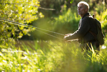 Man With Backpack Fly Fishing With Pole Among Sunny Grass