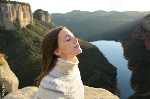 Fototapeta Woman breathing fresh air in a cliff in the mountain obraz
