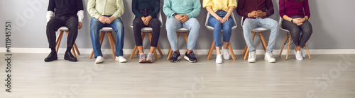 Cropped image of unrecognizable people sitting in the waiting room on chairs in line. Group of unidentified people in casual clothes are waiting their turn for an interview or a doctor's appointment.