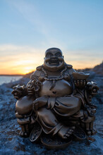 Buddha Figure On Some Rocks, In The Sunset, On The Sea
