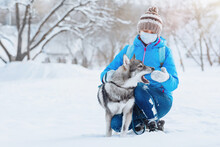 A Woman Wearing A Protective Mask Walks With Her Dog In The Winter Outdoors Due To The Covid-19 Coronavirus Pandemic