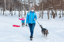 A Girl Wearing A Protective Mask Walks With Her Dog In The Winter Outdoors Due To The Covid-19 Coronavirus Pandemic