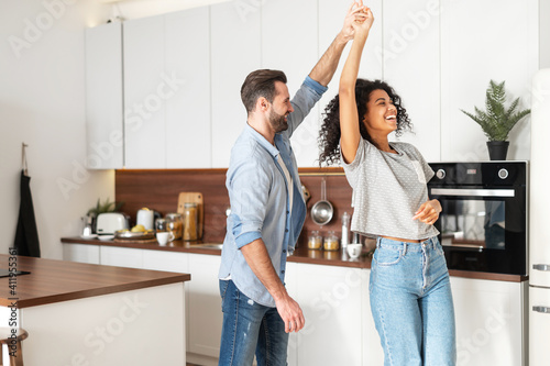 Obraz Handsome white man and attractive African American young woman is cooking and having fun together while cooking on the kitchen, romantic interracial couple is dancing while preparing lunch or dinner - fototapety do salonu