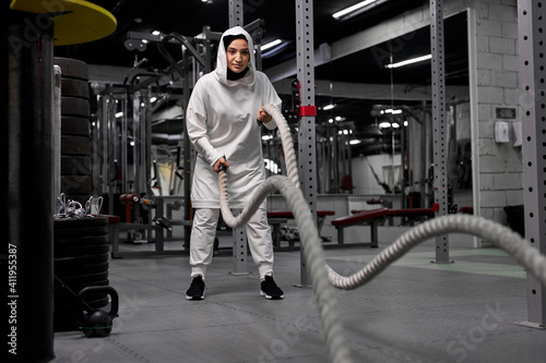 Fototapeta powerful arabic woman Cross Fit trainer in hijab do battle workout with ropes at