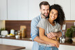 Leinwandbild Motiv Smiling man hugging from behind charming African American woman, two people standing and joyfully looking at camera. Young international couple happily spending time in cozy modern kitchen at home.