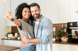 Leinwandbild Motiv Young interracial married couple homeowners smiling, showing keys from a new apartment, hugging and looking at the camera, standing in the kitchen and celebrating moving in a new home, family concept