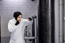 Muslim Sportswoman Engaged In Kickboxing, Hitting A Huge Punching Bag, Wearing Hijab. Young Strong Arabic Woman Boxer Training Hard.