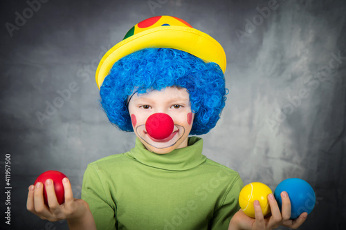 Canvas young child dressed as a clown with wig and fake nose has fun playing with color