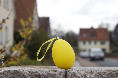 Fotografie, Obraz Close-up Of Yellow Easter Egg On Retaining Wall Against Building