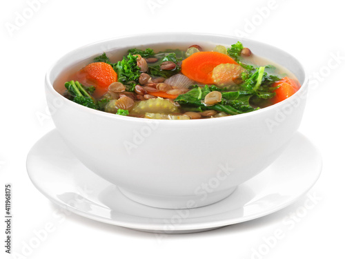 Homemade kale and lentil soup in a white bowl with saucer. Side view isolated on a white background. © Jenifoto