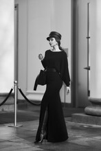 Elegant Woman In Stylish Black Maxi Dress And Cap Posing Outside Exquisite Building