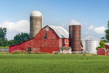On The Other Side Of A Field Of Crops, An Old Red Barn Is Surrounded By Silos And Other Buildings And Agricultural Equipment On A Rural Ohio Farm In The American Midwest.