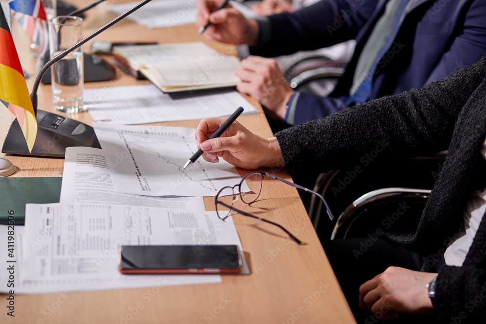 Fototapeta close-up photo of people sitting at desk taking notes, with documents, press conference. business or political meeting in boardroom