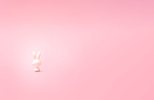 A Lonely Toy Rabbit Sitting And Staring In Pastel Pink Distance. Photo Of Its Back.