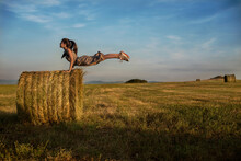 A Teenage Girl Balancing On Her Hands Mid Air On A Hay Bale In A Field, Bulgaria