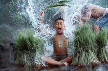Boy Sitting On A Jetty Being Splashed With Water By His Father, Thailand