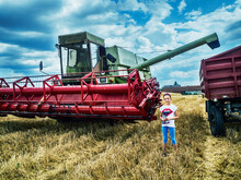 Smiling Girl Standing In A  Wheat Field By A Combine Harvester, Poland
