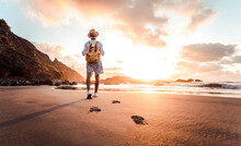 Man With Backpack Walking On The Beach At Sunset - Travel Lifestyle Concept - Golden Filter