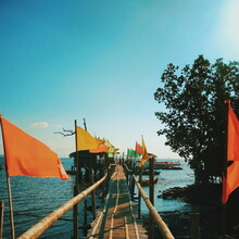 Flags On Pier Over Sea Against Blue Sky