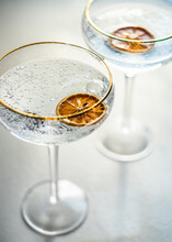 Two Glasses Of Champagne With Slices Of Dried Orange