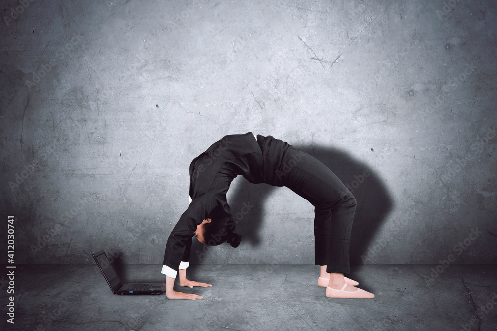 Fototapeta Woman Using Laptop While Dancing Against Wall