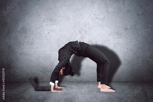 Fototapeta Woman Using Laptop While Dancing Against Wall