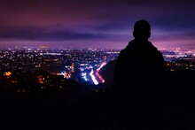Rear View Of Silhouette Man Looking At Illuminated Cityscape Against Dramatic Sky At Night