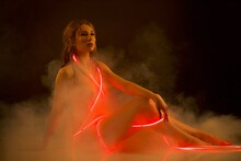 Graceful Naked Woman With Red Neon Light Stripe In Studio