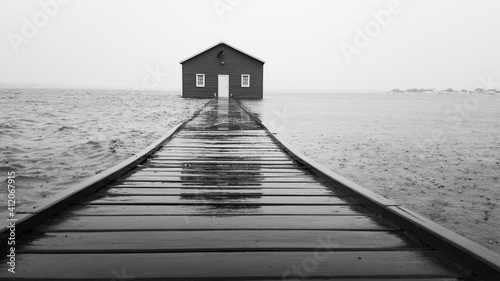 Foto Blue boathouse during rain and high tide
