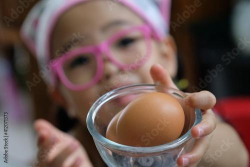 Fototapeta Close-up Portrait Of Girl Holding Egg