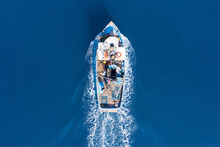Small Fishing Boat Sailing Across Calm Smooth Sea, Aerial View.