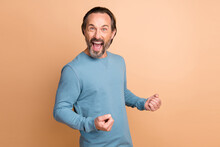 Photo Of Cheerful Excited Guy Shout Open Mouth Hold Fists Wear Blue Sweater Isolated Beige Color Background