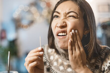 Asian Woman Has A Toothache After A Big Meal And She Pulls Out The Remains Of Food From The Cavity In Her Teeth With A Toothpick. The Concept Of Dental Health And Cleaning