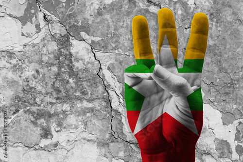 The 3-finger raised as a protest sign with a painted flag of Myanmar фототапет