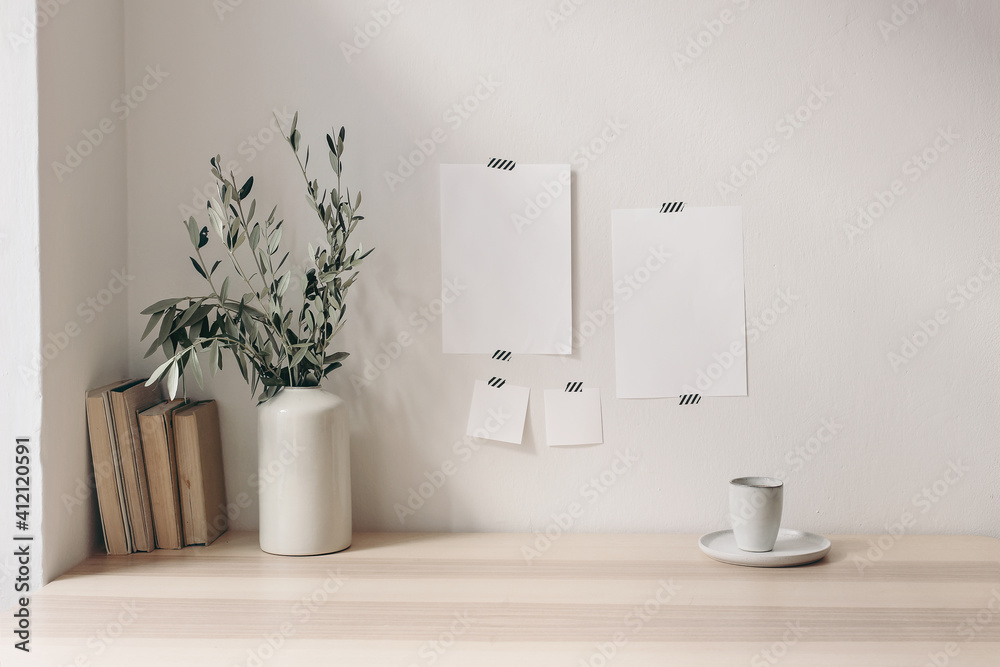 Fototapeta Breakfast still life. Cup of coffee, books on wooden desk, table. Empty notepads and posters mockups taped on white wall.Vase with olive branches. Elegant Scandinavian working space, home office.