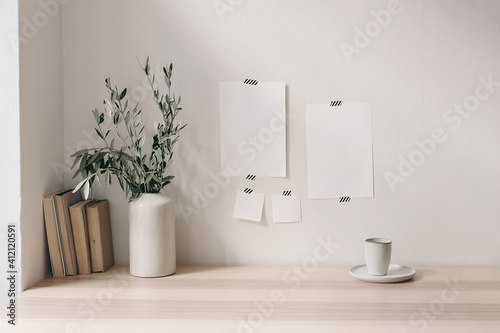 Fototapeta Breakfast still life. Cup of coffee, books on wooden desk, table. Empty notepads and posters mockups taped on white wall.Vase with olive branches. Elegant Scandinavian working space, home office. obraz
