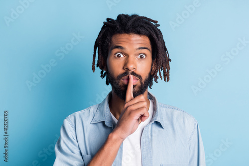 Fototapeta Portrait of nice suspicious guy showing shh sign dont speak isolated over vibrant blue color background obraz